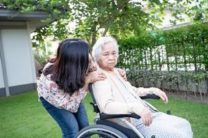 Ayude a la anciana asiática mayor o anciana en silla de ruedas eléctrica y use una mascarilla para proteger la infección de seguridad Covid 19 coronavirus en el parque foto