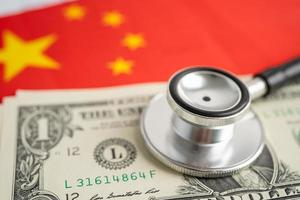 Black stethoscope on China flag background with US dollar banknotes, Business and finance concept. photo
