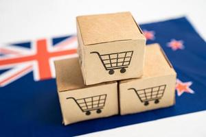 Box with shopping cart logo and New Zealand flag, Import Export Shopping online or eCommerce finance delivery service store product shipping, trade, supplier concept. photo