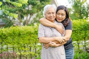 anciana asiática con cuidadora hija caminando y abrazo con feliz en el parque natural. foto