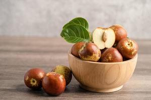 azufaifo o fechas chinas en un tazón de madera, comida sana. foto