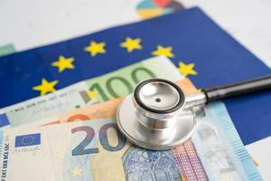 Black stethoscope on EU flag in europe with banknotes money, Business and finance concept. photo