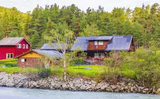 El agua de deshielo turquesa fluye en un río a través de la aldea de Noruega foto