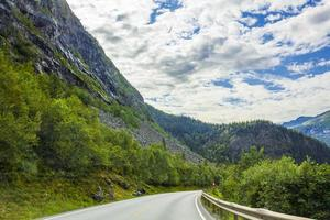 Driving through Norway in summer with mountains and fjord view photo