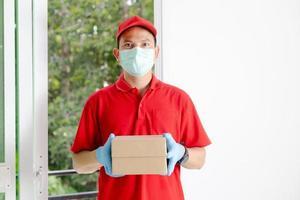 un repartidor con un vestido rojo sostiene una caja de paquetería. foto