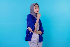mysterious woman makes silence gesture looks away tells secret wearing hijab isolated over white wall photo