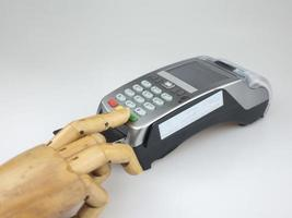 Wooden hand over EDC machine or credit card terminal to made online payment. photo
