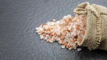 Sal rosa del Himalaya en bolsa de arpillera sobre fondo de piedra negra. concepto saludable. foto
