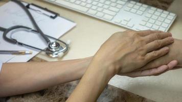 médico o enfermera consolando y apoyando al paciente. foto