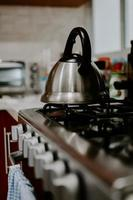Selective focus shot of tea kettle with boiling water on a gas stove photo