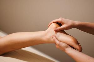 Closeup shot of a masseuse massaging a client's foot photo