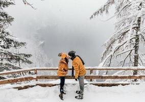 una pareja joven comparte un beso en un clima nevado foto