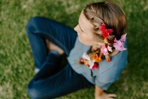 Top view of a blonde female with a braid hairstyle with colorful flowers photo