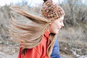 mujer joven con un sombrero con el pelo soplando por el viento foto