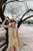 Disparo vertical de una señorita que llevaba un sombrero de playa, gafas de sol y vestido de verano sobre un traje de baño foto