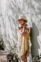 Hermosa joven con un sombrero de playa, vestido de playa y gafas de sol posando apoyado en una pared foto