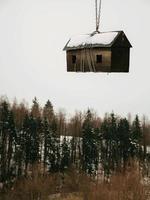 Disparo vertical de un nido de madera colgando sobre el bosque con cadenas foto