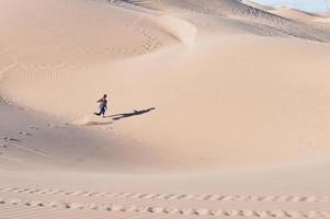 High angle shot of a female running on sand dunes in a desert photo