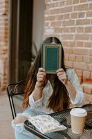 Closeup shot of a South Asian young woman in the cafe covering her face with a book photo
