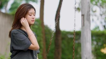 Beautiful Asian woman listening to music while sitting on swings outdoors in her home garden. video