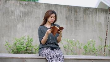 une adolescente asiatique lit un livre assis sur une balançoire dans son jardin. video