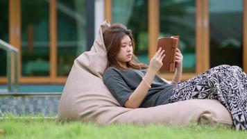 A beautiful Asian woman enjoys listening to music with earphones and reading a book with feeling happy and relaxed in the outdoors in her home garden. video
