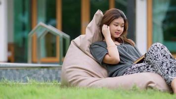 A beautiful Asian woman enjoys listening to music with earphones with feeling happy and relaxed in the outdoors in her home garden. video