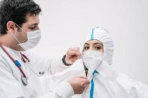Medic putting on protective costume during COVID 19 epidemic photo