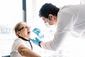 Doctor taking coronavirus test from elderly woman photo