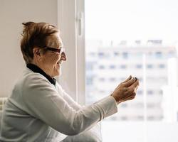 Positive elderly woman talking on video chat at home photo