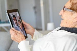 Contenido anciana hablando por video chat en tableta foto