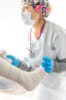 Nurse bandaging leg of patient photo