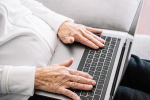 Crop elderly woman using laptop at home photo