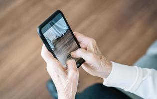 Elderly woman using smartphone at home photo
