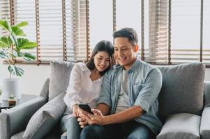 Asian couple using smartphone sitting on sofa photo