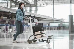 Mujer turista asiática caminando con carrito de equipaje foto
