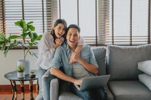 Happy Asian couple using laptop on sofa at home photo