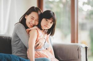 Happy Asian mother and cute little daughter having fun photo