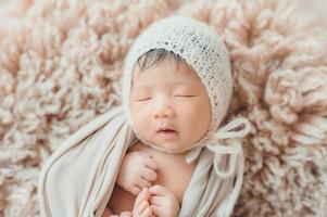 Bebé recién nacido asiático con gorro de punto durmiendo foto