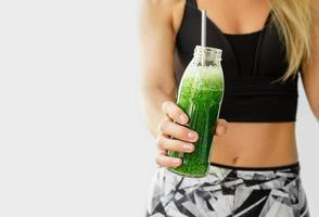 Healthy lifestyle concept. Fitness woman holding a bottle of broccoli and spinach smoothie. Copy space photo
