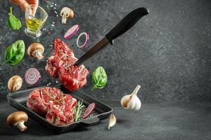Filete de hueso de ternera cruda cayendo sobre la parrilla con ingredientes para cocinar sobre fondo oscuro. copie el espacio. foto