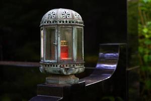 Linterna de tumba envejecida antigua en una tumba distinguida con lápida negra foto