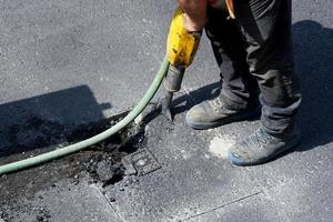 prising up the asphalt of a road with a jackhammer photo
