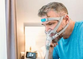 Unhappy shocked man with chronic breathing issues surprised by using  CPAP machine sitting on the bed in bedroom. Healthcare, CPAP, Obstructive sleep apnea therapy, snoring concept photo
