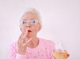 Old fashioned senior stylish woman smoking cigarette with glass of white wine. Bad habit, addiction concept photo