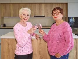 two stylish senior women in pink sweaters drinking rose wine at modern kitchen gossiping. Friendship, talk, gossip, event, relationships, news, family concept photo