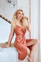 Beautiful Caucasian trendy woman in brown dress sitting by the mirror on the table in modern living room. Cocktail party, style, fashion concept photo