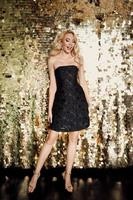 Beautiful blonde caucasian woman in little black dress on the party on golden background.  Party, event, disco, celebration concept photo