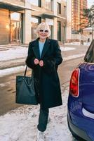 senior stylish woman in elegant black coat and hand bag walking from her car to business appointment. Business, style, anti age concept photo