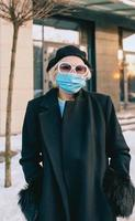 senior stylish woman in beret and elegant black coat and in medical mask walking outdoor. Lockdown, pandemic, protection concept photo
